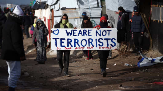 Migrants carry a placard as part of the 'jungle' migrant camp is cleared on February 29, 2016 in Calais, France The French authorities have begun dismantling part of the migrant encampment in the northern French town of Calais and relocating people to purpose-built accommodation nearby.