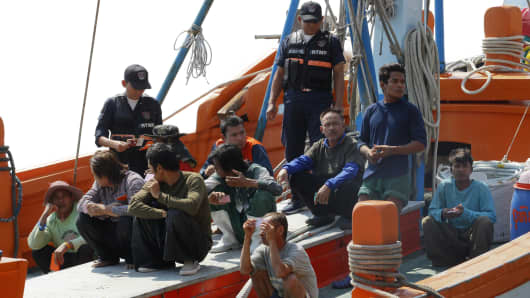 Marine policemen inspect papers of migrant workers after a fishing boat arrives at a port in Thailand.