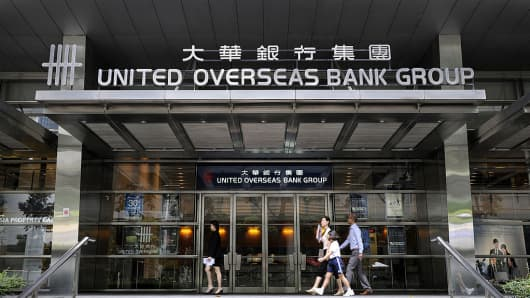 Pedestrians walk past a United Overseas Bank (UOB) branch in Singapore.
