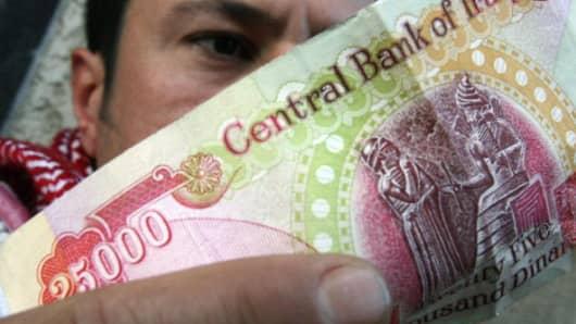An Iraqi man checks the authenticity of a 25,000-dinar bill.