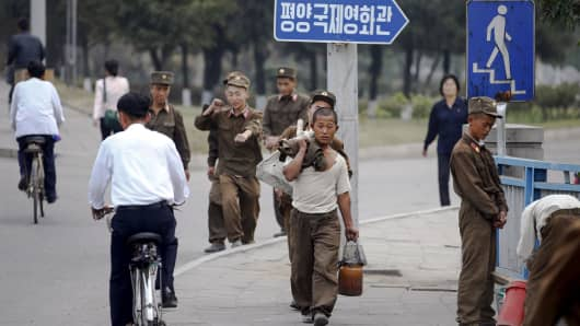 """Soldier-builders"" and civilians walk in central Pyongyang, North Korea last October."