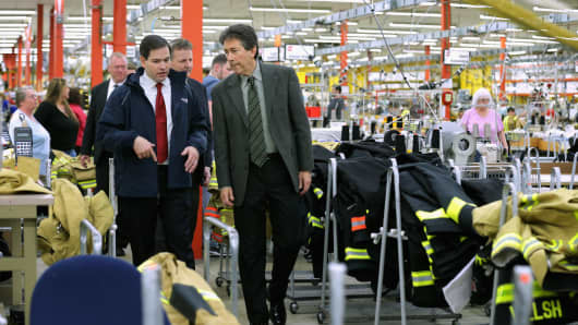 Republican presidential candidate Sen. Marco Rubio (R-FL) (L) is given a tour of Globe Manufacturing by President and CEO Don Welch before holding a town hall event with employees February 3, 2016 in Pittsfield, New Hampshire.