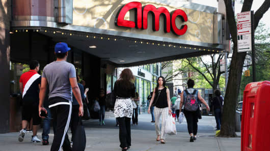 Pedestrians pass by an AMC movie theater in New York.