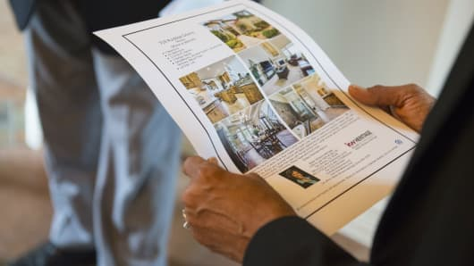A realtor reviews a listing before taking prospective home buyers on a tour of a house in Helotes, Texas.