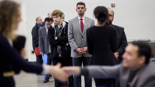 Job seekers wait in line to speak with company representatives during a Choice Career Fair event in Seattle.