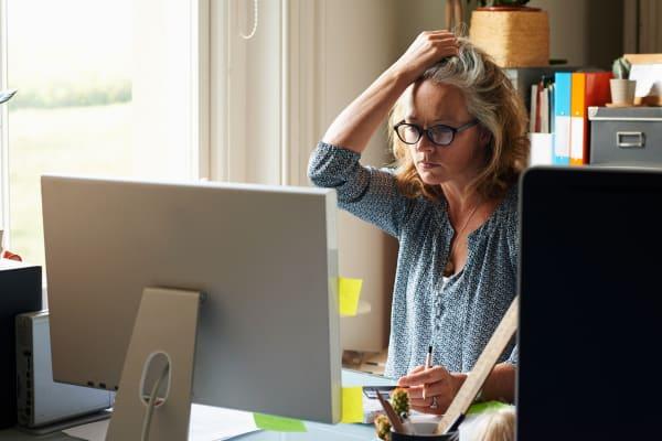 Destacó la mujer con la mano en el pelo con tarjeta de crédito en la computadora en la oficina en casa