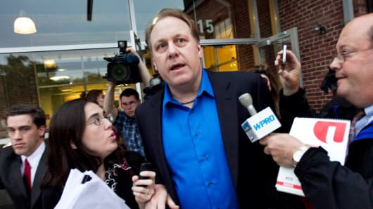 Former Boston Red Sox pitcher Curt Schilling, center, is followed by members of the media as he departs the Rhode Island Economic Development Corporation in Providence, R.I., May 21, 2012.