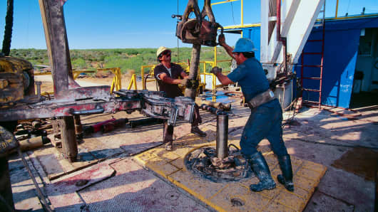 Oil workers moving a drill on a rig in Texas.
