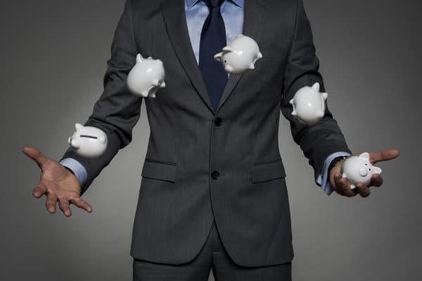 Financial businessman juggling piggy banks