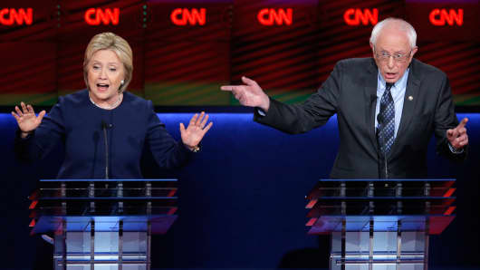 Democratic U.S. presidential candidates Hillary Clinton and Bernie Sanders speak simultaneously as they debate during the Democratic U.S. presidential candidates' debate in Flint, Michigan, March 6, 2016.