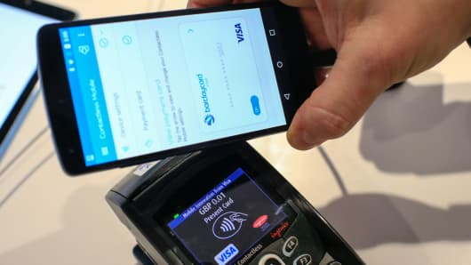 A worker demonstrates a mobile payment system at the Visa stand at the Mobile World Congress in Barcelona, Spain last February.