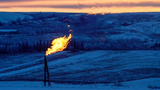 A natural gas flare on an oil-well pad burns as the sun sets outside Watford City, North Dakota