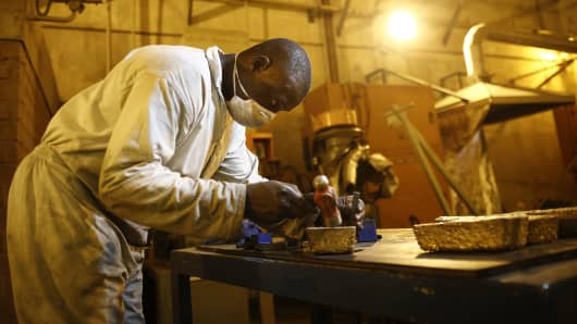 A worker uses a hammer and a letter punch to engrave gold bars at the Kibali gold mine, operated by Randgold Resources Ltd., in Kibali, Democratic Republic of Congo.