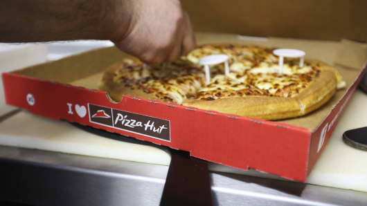 An employee places plastic box supports around a freshly cooked pizza as he prepares a takeaway order for a customer, in the kitchen of a Pizza Hut restaurant, owned by Yum! Brands Inc.