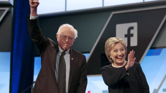 Democratic U.S. presidential candidates Senator Bernie Sanders and Hillary Clinton wave before the start of the Univision News and Washington Post Democratic U.S. presidential candidates debate in Kendall, Florida, March 9, 2016.
