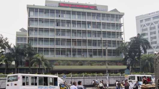 Commuters pass by the front of the Bangladesh central bank building