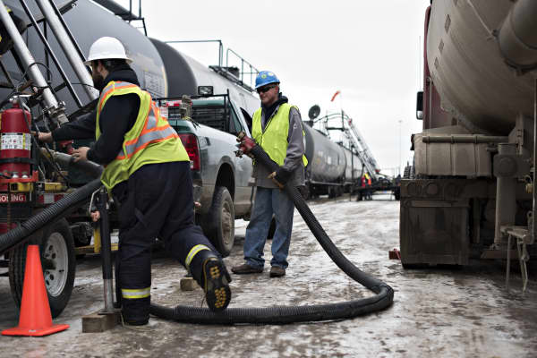 A truck driver holds a supply line while preparing to transload liquid propane from his truck to a rail car at the Red River Supply rail yard in Williston, North Dakota.