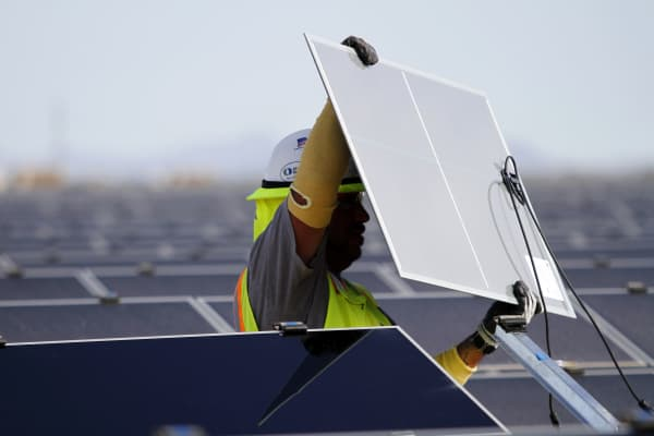 A worker installs First Solar Inc. photovoltaic solar panels at the Agua Caliente Solar Project in Yuma County, Arizona.