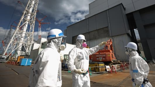 Workers outside Reactor 4 work to decontaminate the Tokyo Electric Power Co.'s Fukushima Daiichi nuclear power plant on Feb. 25, 2016, in Okuma, Japan.