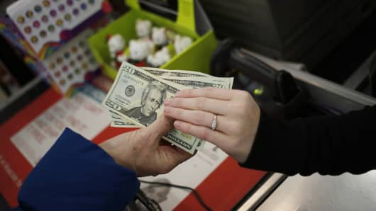 A customer, left, hands over U.S. twenty dollar bills as she pays for her purchases in Frankfurt, Kentucky.