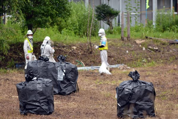 A July 2015 photo of clean-up workers decontaminating the village of Iitate in Fukushima prefecture. Iitate was directly in the path of a radiation plume set off by the meltdown at the nuclear plant in 2011.