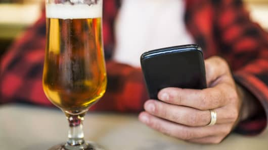 Phone in hand at a bar with a beer