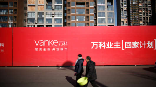 Two citizens pass by Vanke's buildings near the explosion site happened on August 12 at Tianjin Binhai New Area which brought at least 165 people including workers, citizens and firefighters into death on February 4, 2016 in Tianjin, China.
