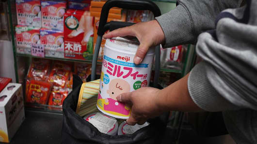 A man packs tins of Japanese milk powder into a shopping bag at a store in the Kowloon district of Hong Kong on March 16, 2011.