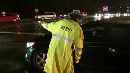 In this photo provided by ABC11, an Alamance County Sheriff Dept. officer directs traffic near exit 154 on Interstate 40 after multiple vehicle accidents Sunday, March 13, 2016, in central North Carolina.