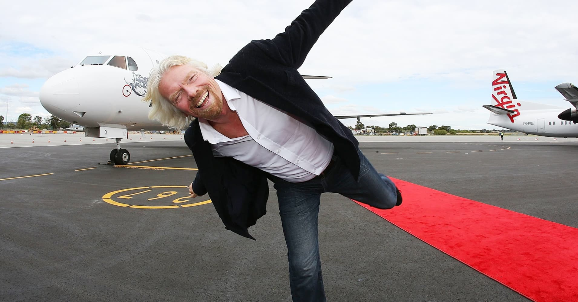 Sir Richard Branson poses in front of an aircraft at Perth Airport on May 7, 2013 in Perth, Australia.