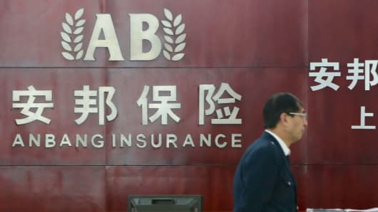 A Chinese security guard walks past the front desk at a branch of Anbang Insurance in Shanghai last December.