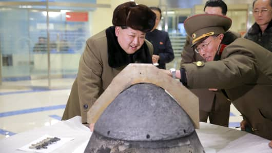 North Korean leader Kim Jong Un looks at a rocket warhead tip after a simulated test of atmospheric re-entry of a ballistic missile, at an unidentified location in this undated photo released by North Korea's Korean Central News Agency (KCNA) in Pyongyang on March 15, 2016.