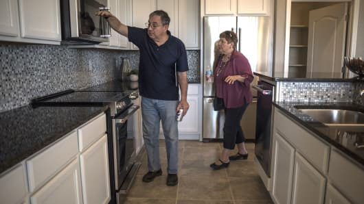 Prospective home buyers view a kitchen while touring a model home at a PulteGroup housing development in Albuquerque, New Mexico.