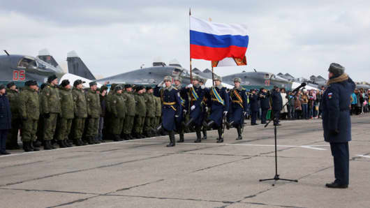 In this photo provided by the Russian Defense Ministry Press Service, guards walk past a lineup of troops during a welcome ceremony for Russian military personnel who returned from Syria at an airbase near the Russian city Voronezh, Tuesday, March 15, 2016.