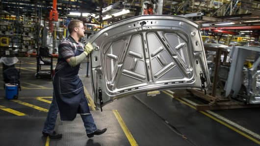 An employee prepares to install the hood on a sports utility vehicle at the General Motors assembly plant in Arlington, Texas.