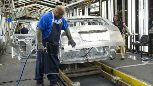 An employee uses a flash grinder to smooth out the frame of a sports utility vehicle at the General Motors assembly plant in Arlington, Texas.