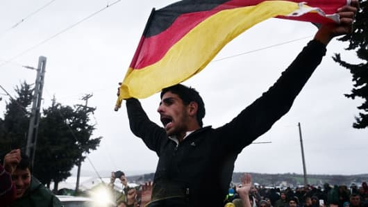 A man holds a German flag as migrants and refugees protest for the opening of borders near the Greek village of Idomeni, where thousands are stranded on March 7, 2016.