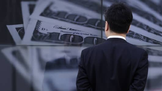 A businessman looks at a screen displaying a photo of U.S. $100 bank notes in Tokyo.
