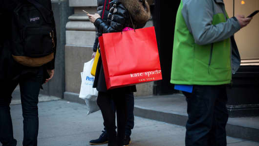 A shopper carries a Kate Spade bag outside a store in New York.