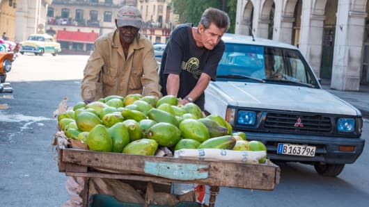 Cuban fruit and vegetable sellers push a handcart of avocados for sale in downtown Havana, Cuba.