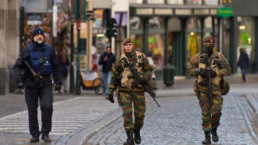 An armed policeman and two soldiers guard the shops on Rue Du Marche Aux Herbes on November 23, 2015 in Brussels, Belgium.