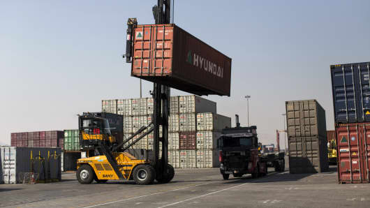 A crane loads a shipping container onto a truck at Shahid Rajaee port, some 20 kms west of Gulf port city of Bandar Abbas on February 21, 2016.