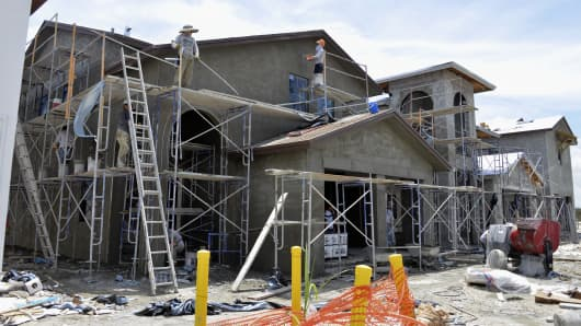 A stucco crew plasters the exterior of a new two-story home at the Lennar Corp. Madison Pointe at Central Park development in Doral, Florida.