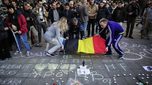 People display the Belgian flag at Beursplein Square after Tuesday's attack in Brussels.