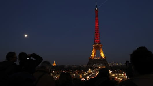 People look at the Eiffel Tower in Paris illuminated in colours of the Belgian flag in tribute to the victims of terrorist attacks in Brussels on March 22, 2016.