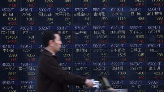A cyclist goes past a quotation board flashing share prices of the Tokyo Stock Exchange (TSE) in front of a securities company in Tokyo.