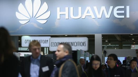 Visitors crowd the Huawei stand at the 2016 CeBIT digital technology trade fair on the fair's opening day.