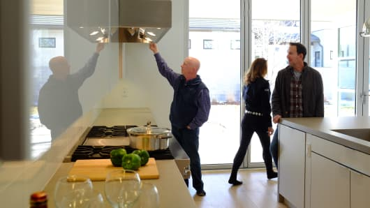 Prospective buyers with their real estate agent survey the kitchen of a new home in Denver.