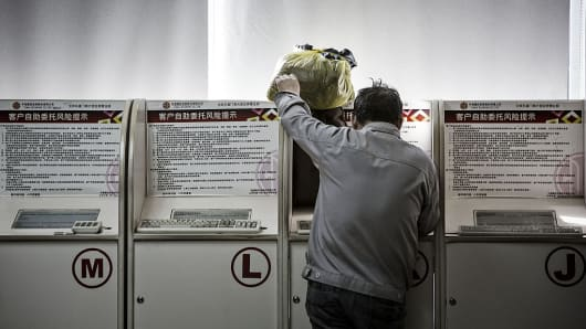 A man stands at a trading terminal of a securities brokerage in Beijing, China.
