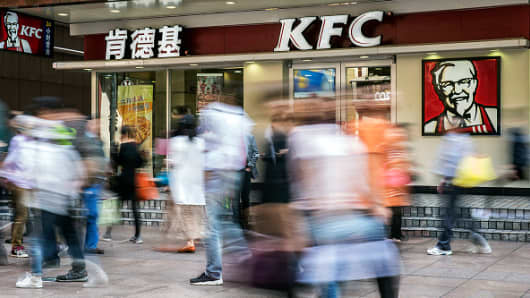 Pedestrians walk past a Yum! Brands Inc. KFC restaurant in Shanghai, China, on Wednesday, Oct. 21, 2015.